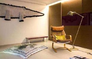 Relax - Canto de descanso e leitura da proprietária, com escultura de jacaré na parede
