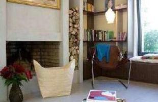 Lareira - Junto à lareira de lenha, prateleiras com livros, poltrona moderna, banqueta sob a janela e quadro