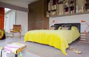 Estilo clean - O quarto do casal tem prateleiras na cabeceira da cama, com livros e objetos de arte
