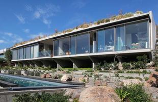 Aos pés de um morro, esta casa chilena se abre em um pavilhão que chega à natureza. A morada lança mão do soprar suave do vento que perpassa todos os ambientes