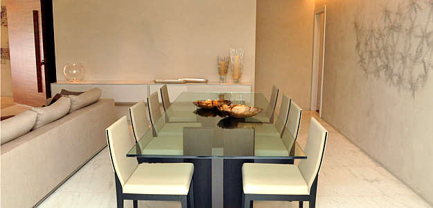 Sala de jantar com parede em stucco se destaca pela textura atemporal