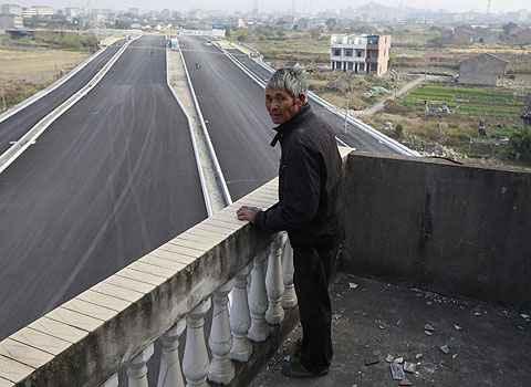 Luo Baogen olha para a estrada que ainda est� para ser inaugurada (Aly Song)