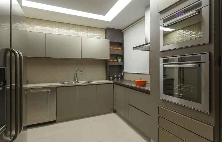 Na cozinha, um armário de 16cm de profundidade por 2,60m de altura foi a solução para deixar tudo organizado - Henrique Queiroga/Divulgação