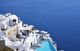 As piscinas valorizam o imóvel e, com a chegada do verão, são festejadas e celebradas por pessoas de todas as idades. Atualmente, elas aparecem com borda infinita, design arrojado e revestimentos modernos e coloridos. Na foto, hotel Katikies, em Santorini, na Grécia