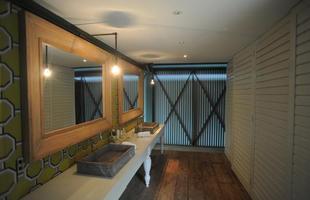 Banho do casal - Também inserido no projeto de reforma, o banheiro ganhou bancada com cubas individuais. Em frente ao espelho, duas portas com divisórias abrigam o chuveiro e os sanitários, ambos em nichos separados
