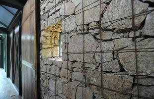 Detalhe - Também revestida em pedra, a construção traz um detalhe interessante: gabião, ou gaiolas de metal. Ideia do arquiteto Carico, o elemento é mais um diferencial do projeto e agrega um aspecto rústico à  casa