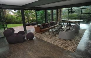 Sala de estar - Imensa, a sala de estar parece ainda mais ampla por ter três das paredes em vidro. Além da vista para a mata, o espaço também revela a área de lazer com piscina, deck e cozinha externa, integradas ao paisagismo