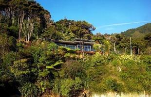 Esta morada de férias na Nova Zelândia se aninha entre a mata nativa e o mar. O projeto seguiu os contornos do terreno acidentado para se misturar à natureza