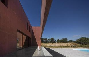 Esta morada em Portugal integra três grandes pátios que são harmonizados ao entorno. A casa alterna ambientes íntimos e privados e outros espaços abertos à natureza