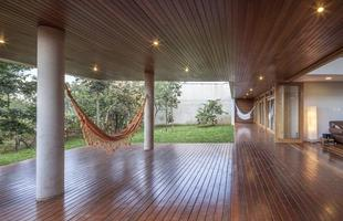 Esta casa em Brasília gira em torno de uma árvore frondosa e alcança a paisagem com bela arquitetura. O imóvel valoriza as montanhas, o cerrado e uma imponente Copaíba