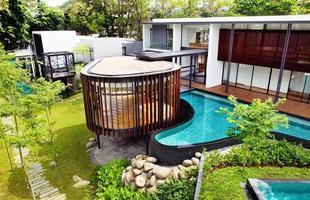 Afastada da rua, esta casa resguarda uma bela arquitetura que se revela em vidro e curvas. A volumetria e um pavilhão suspenso dão forma a distribuição espacial fluida e generosos planos ao ar livre na morada, situada em Singapura