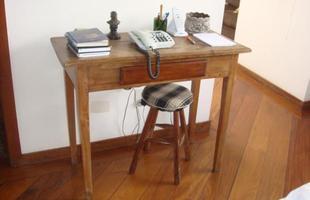Mobiliário antigo pode ganhar nova roupagem para aparecer moderno como estrela da casa. A arquiteta Valéria Alves aproveitou uma mesa velha, lixada e envernizada. O banco recebeu estofamento com almofada de tecido xadrez