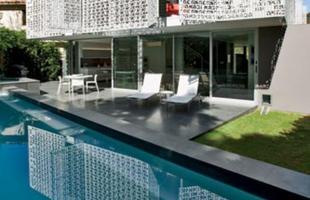 A residência é envolvida por painéis de alumínio com padronagem feita com a palavra Ahava (amor, em hebraico)